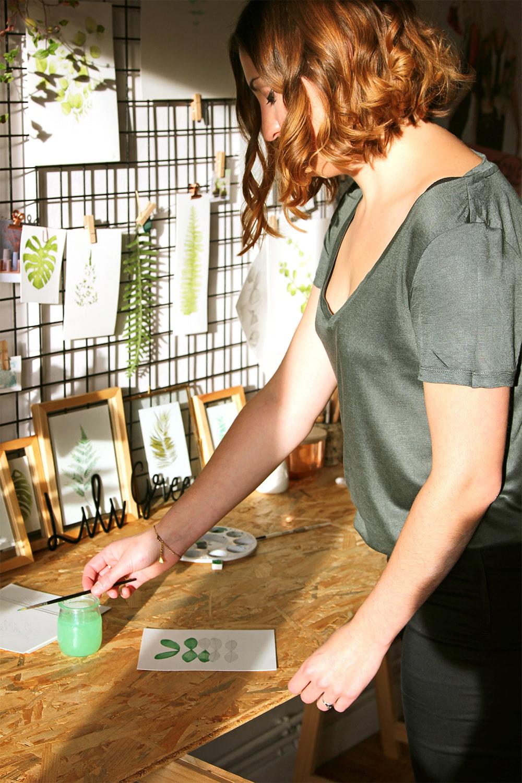 Lili Green dans son atelier, entourée d'aquarelles et de plantes.